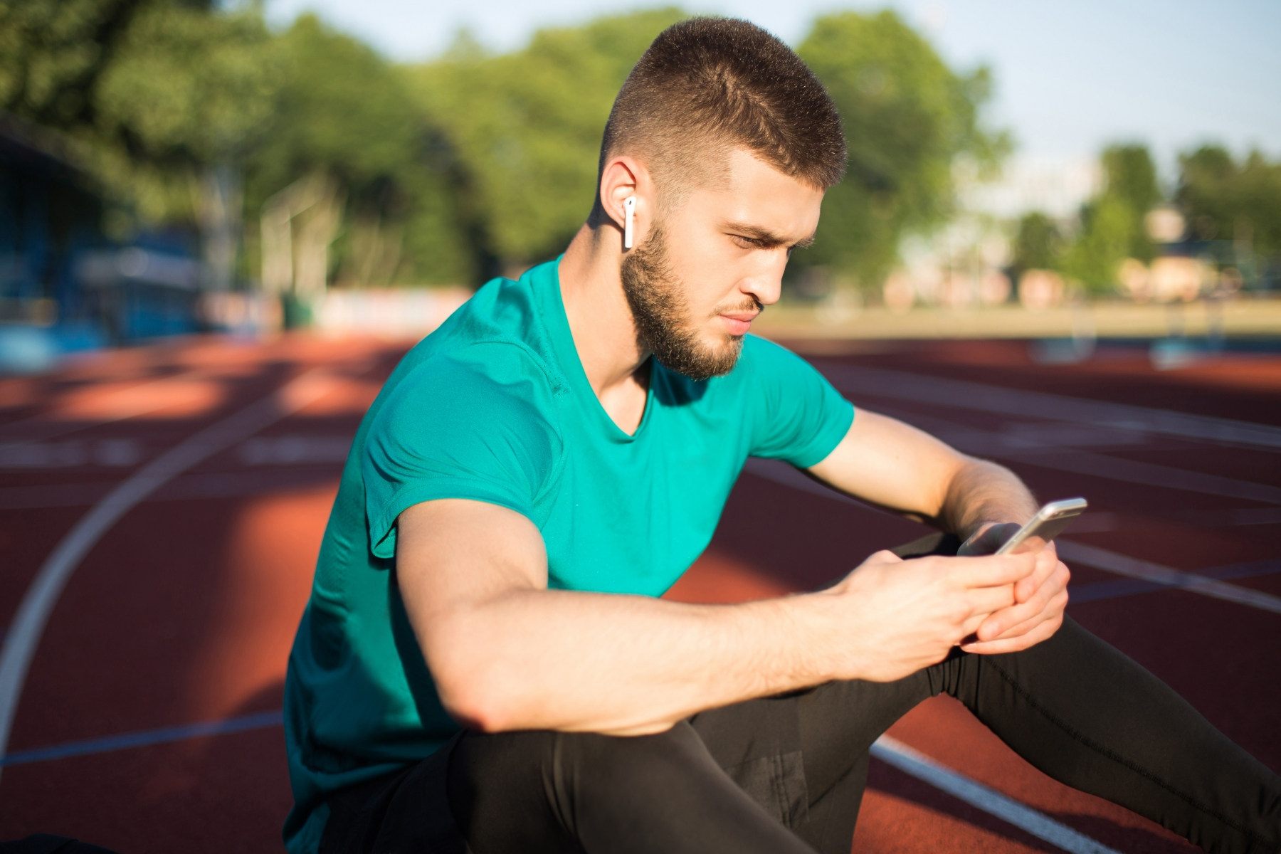 Portrait of man in wireless earphones thoughtfully using cellphone while spending time on running track of stadium