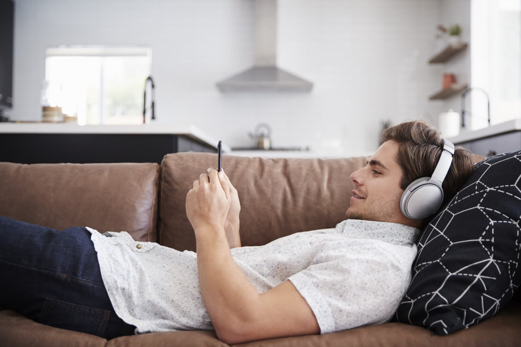 man-wearing-wireless-headphones-lying-on-sofa-at-h-3SGYA4W