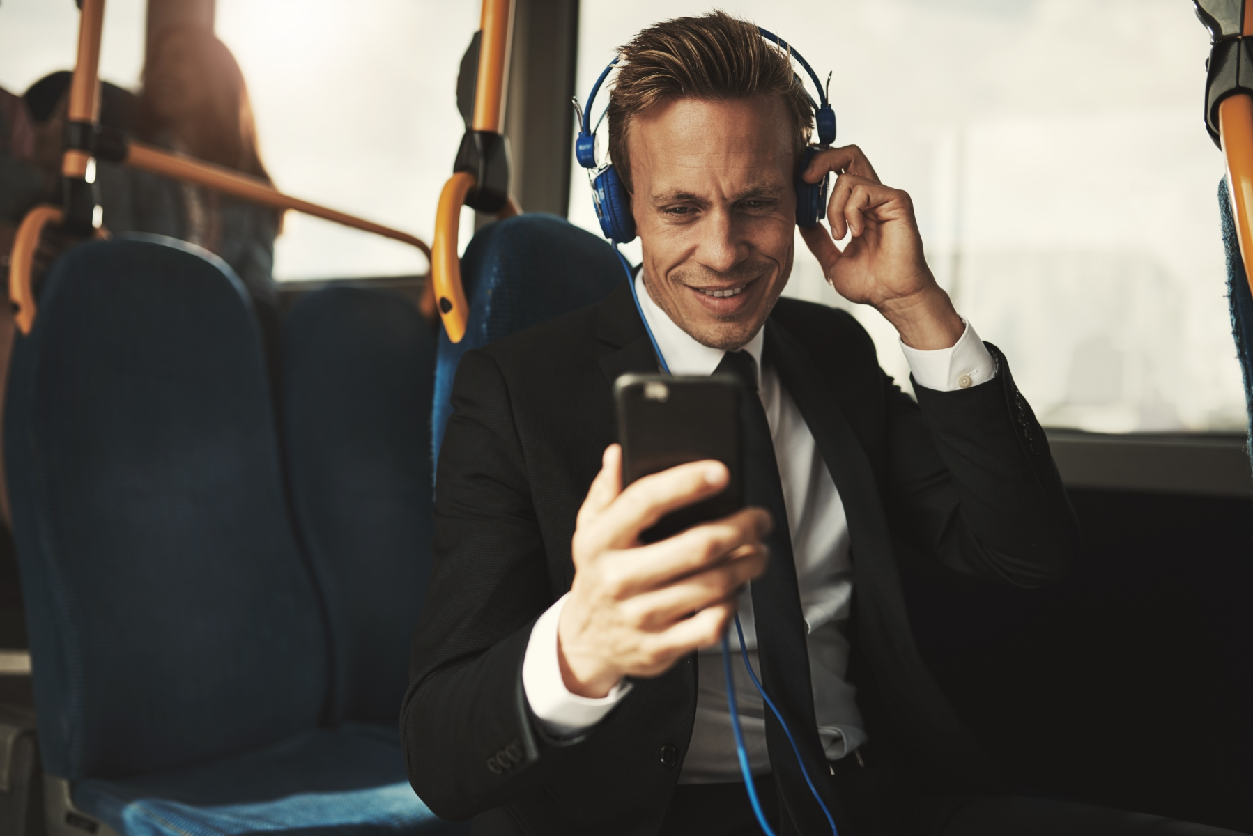 Smiling businessman reading messages and wearing headphones on a bus