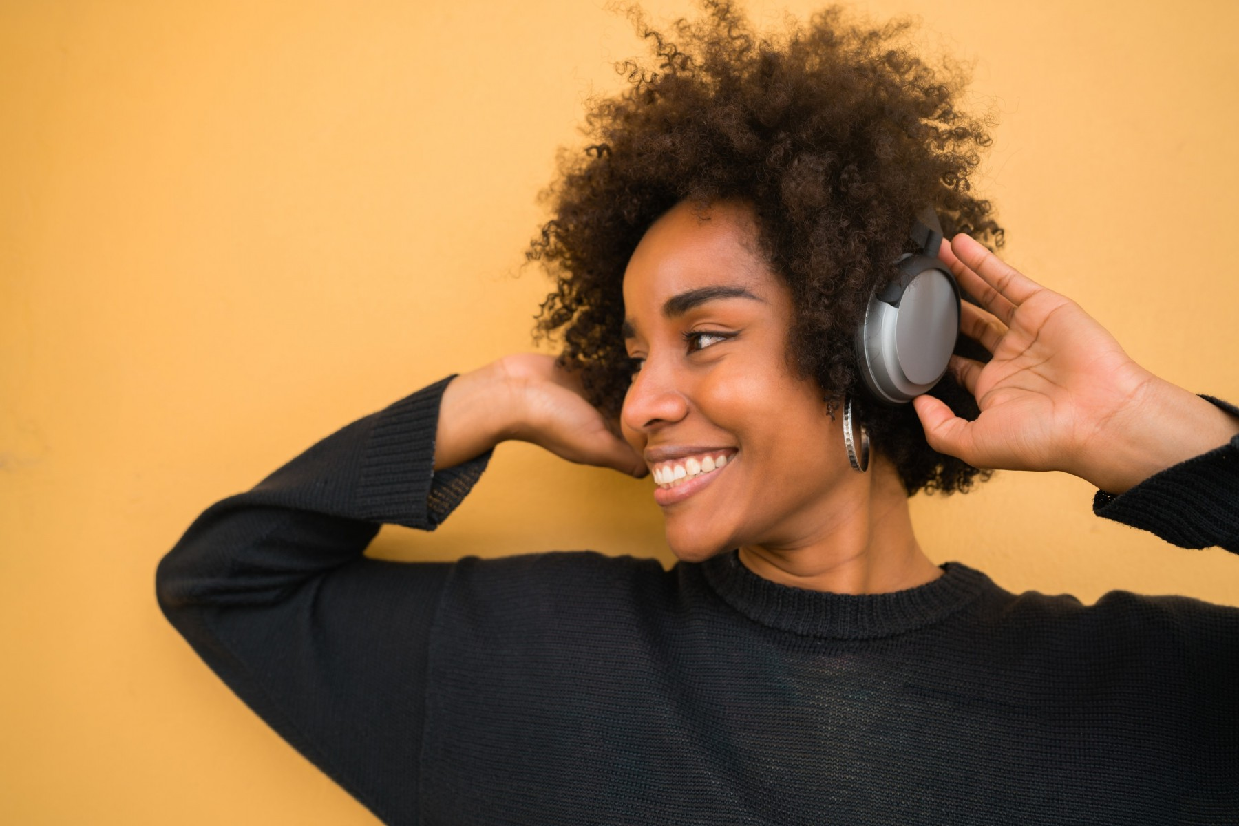 young-afro-woman-listening-to-music-with-headphone-2JEMH22